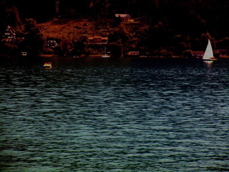 Das gelbe Tretboot und das weiße Segelboot auf dem dunklen Wörthersee