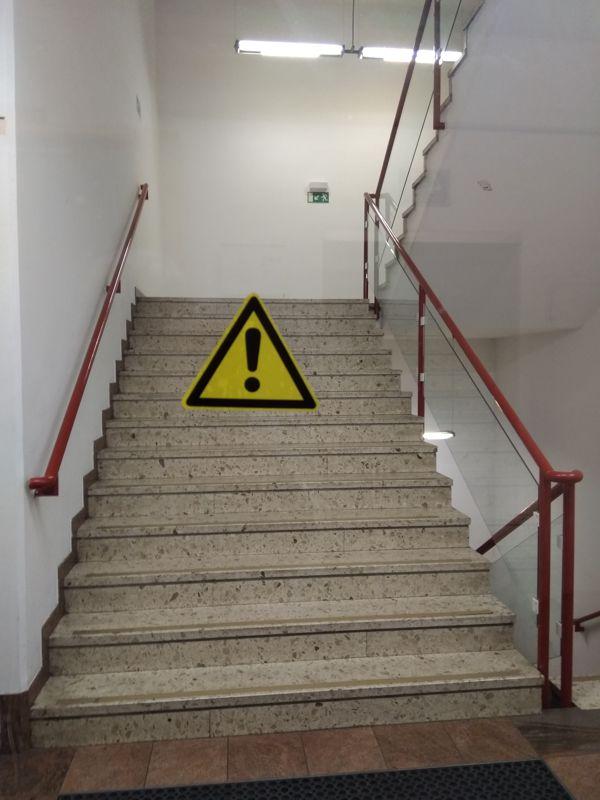 Das gelbe Vorsicht!-Schild schwebt über dem Stiegenhaus mit dem roten Geländer