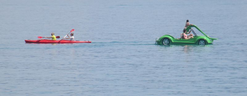 Rotes Paddelboot und grünes Autotretboot