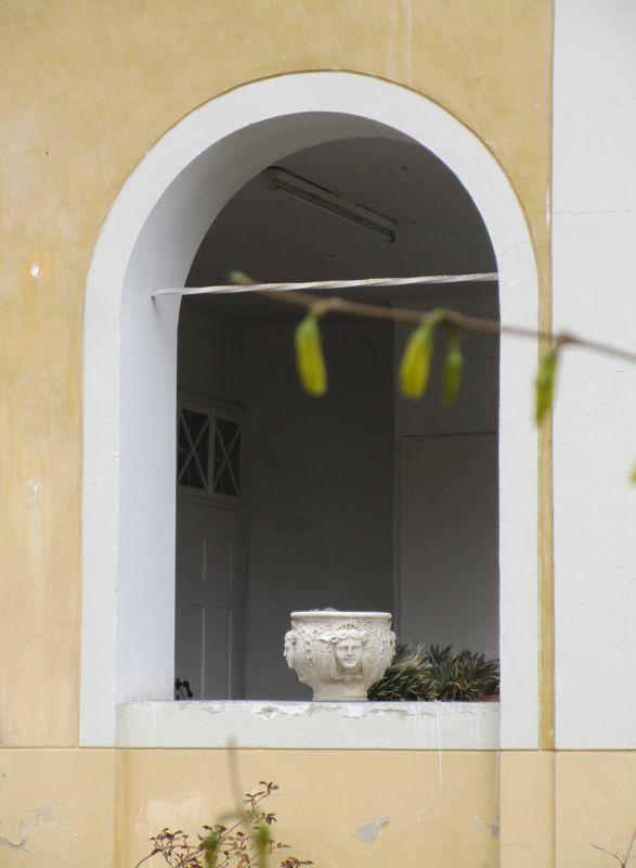 Das weiße Bogenfenster ohne Glas mit der beigen Schale mit vier gleichen Gesichtern