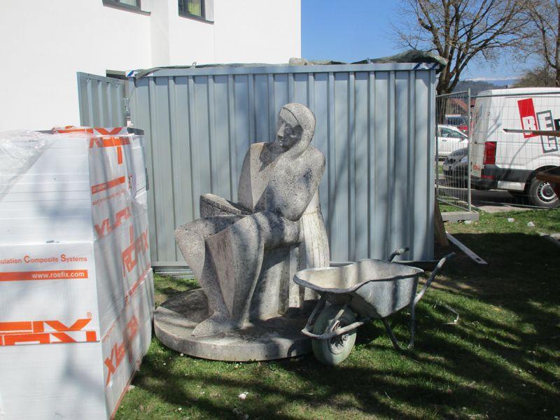 Die Skulptur der sitzenden Frau auf der Baustelle