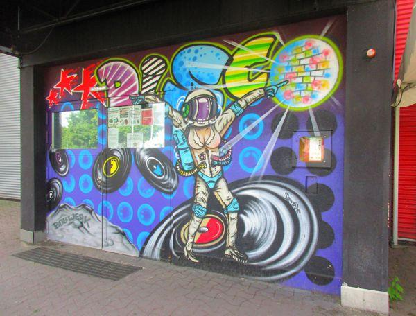 Das Graffito der tanzenden Astronautin und Langspielplatten im Eingangsbereich der Diskothek Bollwerk