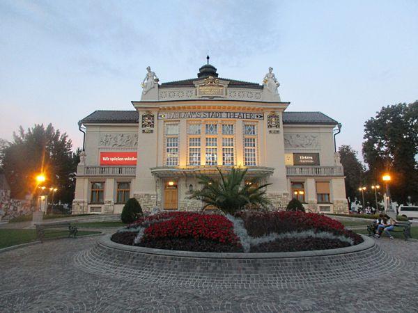 Das Stadttheater Klagenfurt und das junge Liebespaar auf der Sitzbank zur beginnenden Nacht